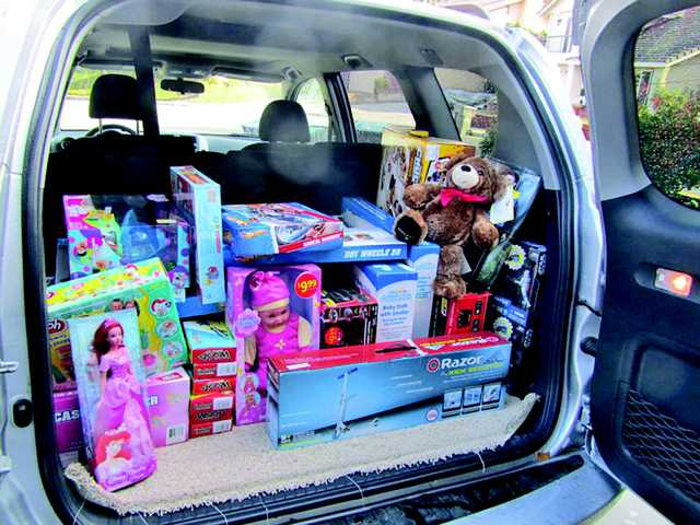 Toys collected by the Zager family are loaded into their car to deliver to the Spark of Love toy drive.
