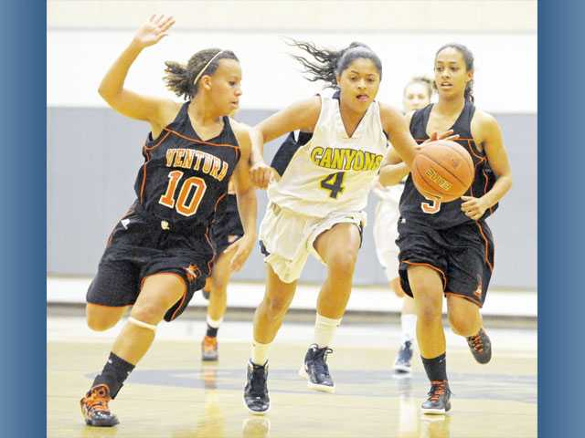 College of the Canyon guard Bev Weaver (4) drives between Ventura College defenders Rebecca Griffin, left, and Regan Mew on Wednesday at COC. Weaver finished the game with 18 points.