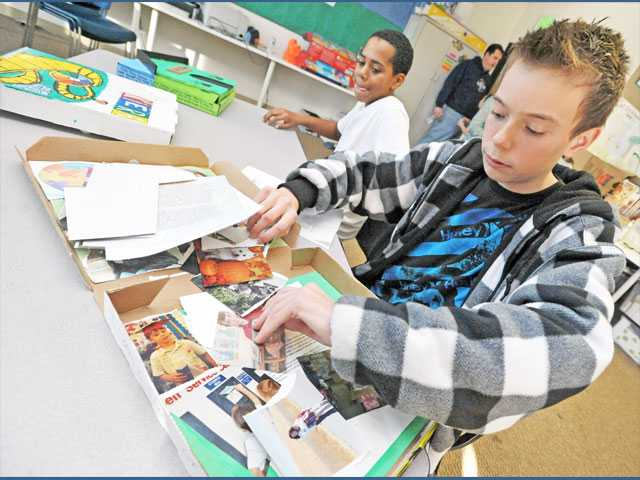 "Seventh-grader Daniel Cox, 13, sorts through family photos in a pizza box as part of his ""A Slice of Me"" project at Santa Clarita Valley International Charter School in Castaic."
