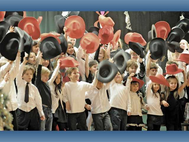 "A hundred Sulphur Springs Community School first-graders tip their cowboy hats as they sing ""Christmas Time's a Comin'"" during the ""Holiday Hats"" presentation for family and friends at Sulphur Springs Community School in Canyon Country on Wednesday."