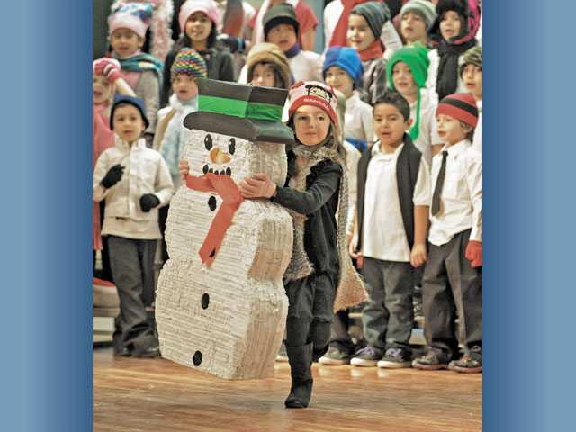 "First-grader Taylor Drake carries a snowman across the stage as four first-grade classes sing ""Frosty the Snowman."""