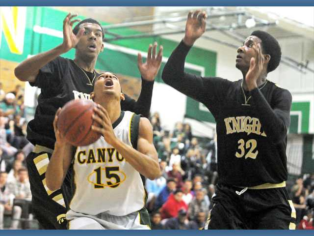 Knight defenders Zack Hollis, left, and Vondel Faniel, right, put pressure on Canyon center Dean Hendrix-Davis as he attempts a shot Friday at Canyon High School.