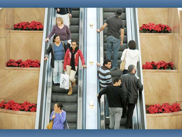 Shoppers are seen on the escalators at Westfield Valencia Town Center on Saturday.