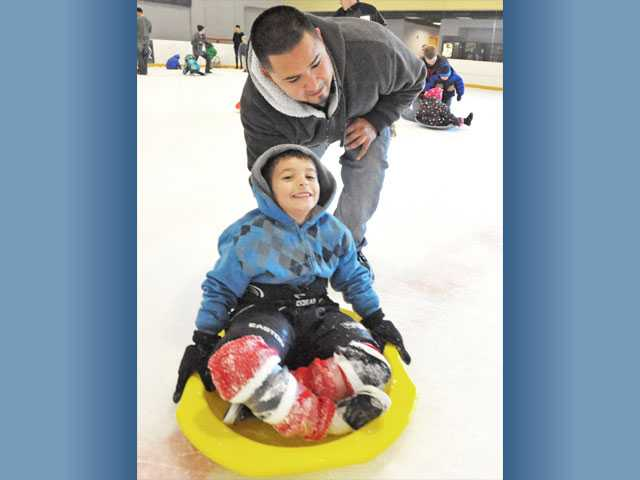 "Oscar Magdaleno, of Valencia, pushes his son Marcos, 5, on a sled at Ice Station Valencia's ""Family Snow Day"" on Saturday."