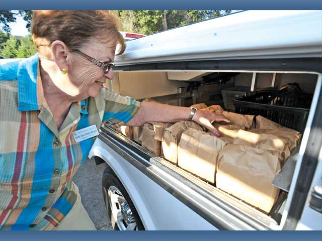 SCV Senior Center volunteer home food delivery driver Jackie Cortes counts the meals in her truck at the SCV Senior Center, which are ready for delivery to seniors, in September.
