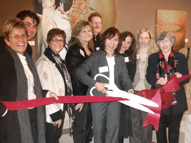 Zony Gordon, president of the Santa Clarita Artists' Association, center, wields the ceremonial scissors during the ribbon cutting held Dec. 12 for the organization's new 1,500-square-foot art gallery at Westfield Valencia Town Center.