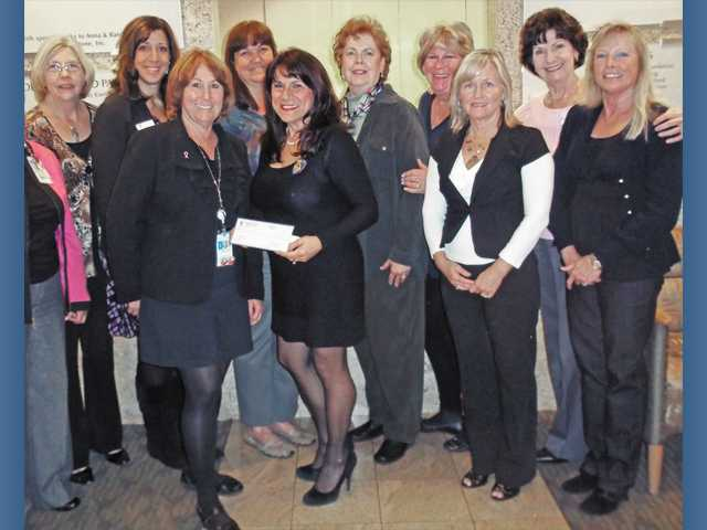 Soroptimist International of Santa Clarita Valley President Sandi Naba, holding check, presents an $8,000 check to Terry Bucknell, director of the Sheila R. Veloz Breast Imaging Center. Soroptimist of SCV members, rear, left to right, Sue Boscamp, Kelly Inga, Cindy Diaz, Karen Ilich, Lori Hollister, Tracy Tait, Kaye Cruger and Patti Golding.