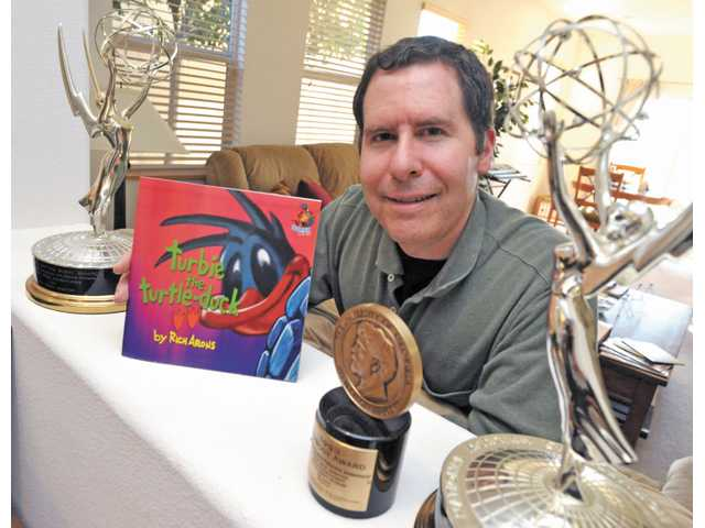 "Arons poses with his debut children's book ""Turbie the Turtle-Duck,"" and the Emmy and Peabody awards he's won."