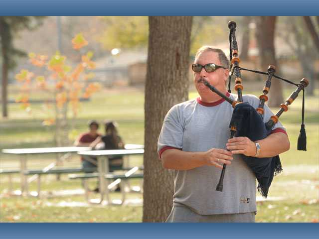A couple sits at a picnic table, left, as Chris Carson, of Canyon Country, practices on his set of bagpipes under the fall colors at Newhall Park on Thursday. Carson, a security guard, has played since 1969, and performs for hire at myriad occasions. He was preparing to perform at a birthday party today.