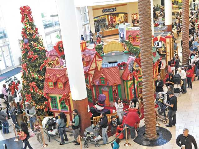 Guests wait to visit Santa Claus at Westfield Valencia Town Center on Saturday.