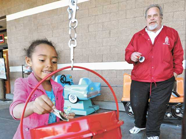 Lily Palmer, 6, of Canyon Country, leaves a donation for the Salvation Army as bell-ringer Gerald Young, 53, of Canyon Country, looks on outside the Stater Bros. supermarket in Canyon Country on Saturday.