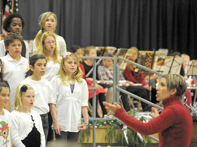 Newhall School District chorus teacher Jami DeSiena, right, leads the chorus during the district's Winter Concert at Pico Canyon Elementary School in Stevenson Ranch on Wednesday.