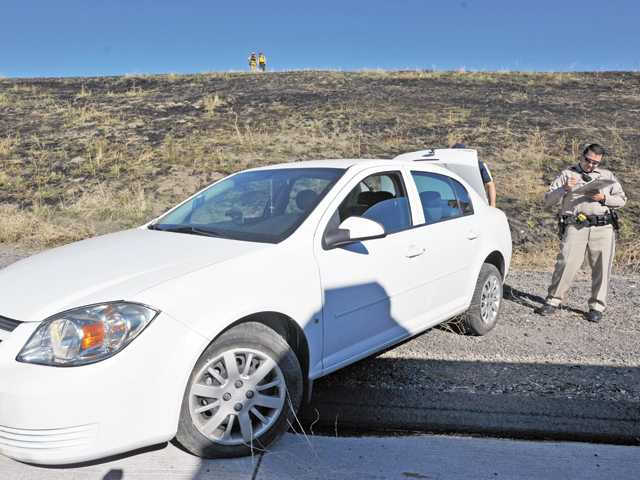 A California Highway Patrol officer investigates a crash that ignited a brush fire on northbound Interstate 5 south of Templin Highway on Monday.