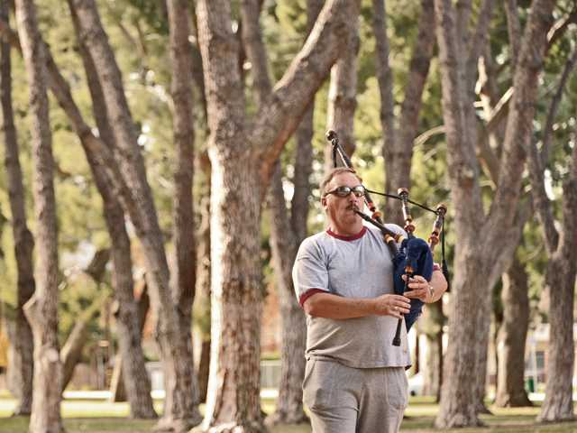 Chris Carson, of Canyon Country, practices on his bagpipes at Newhall Park on Thursday. Carson, a security guard, has played since 1969 and performs for hire at all occasions.