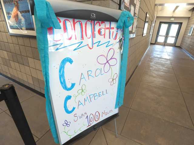 A sign posted at the entrance of the pool congratulates one of the members of the 100-Mile Club who reached 100 miles at the Santa Clarita Aquatic Center in Santa Clarita on Wednesday.