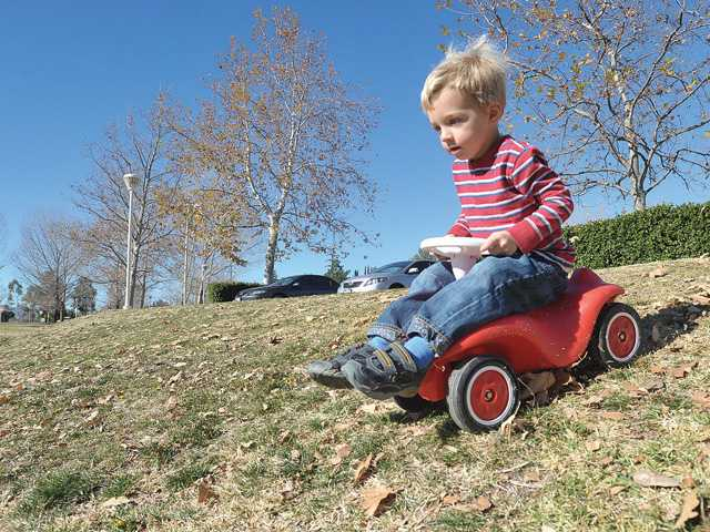 Jannik Schroeder, 2, of Saugus, rides his truck down a hill as he enjoys the 80-degree weather at Central Park in Saugus on Thursday.