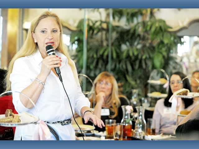 Larraine Segil speaks during the Lunch Mob event at The Tea Gardens in Saugus on Wednesday.