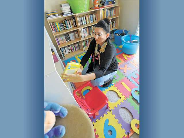 Najarro picks up toys in the child play center in Canyon Country.