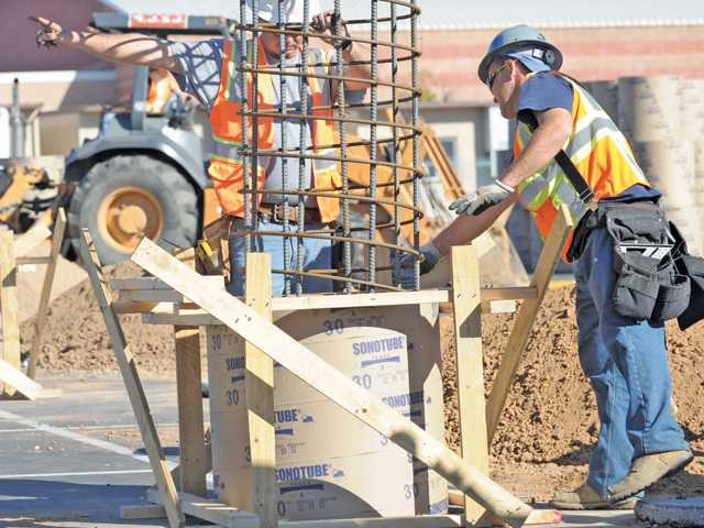 A worker signals a forklift as it lowers a rebar support into a concrete form that will become the base of a 30-foot column that will support hundreds solar panels over the parking spaces in the Valencia High School parking lot during solar panel installation Wednesday.