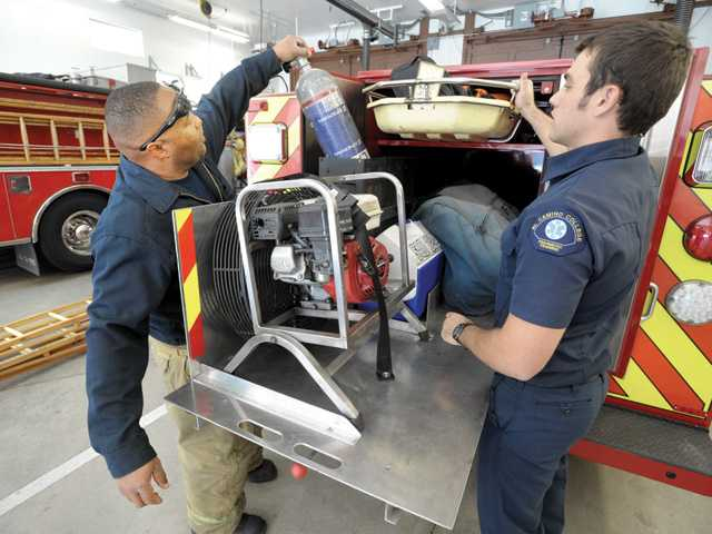 Firefighter/paramedic David Bowman, left, and paramedic intern Steve Nielesky check equipment as they restock Squad 124 after returning from a call responding to a woman who injured her back in a fall from a ladder Dec. 31.