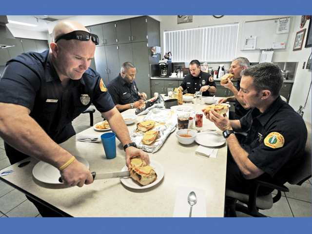Firefighters from left, Tim Koch, David Bowman, Capt. Tom Stukey, Neil Milner and Ryan Chapin sit down to lunch during their 24-hour shift at Fire Station 124.