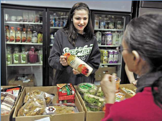 Sara Ludwick, 14, gives a bottle of juice from the dairy and produce section of Help the Children Santa Clarita to a client during food distribution night on Thursday.