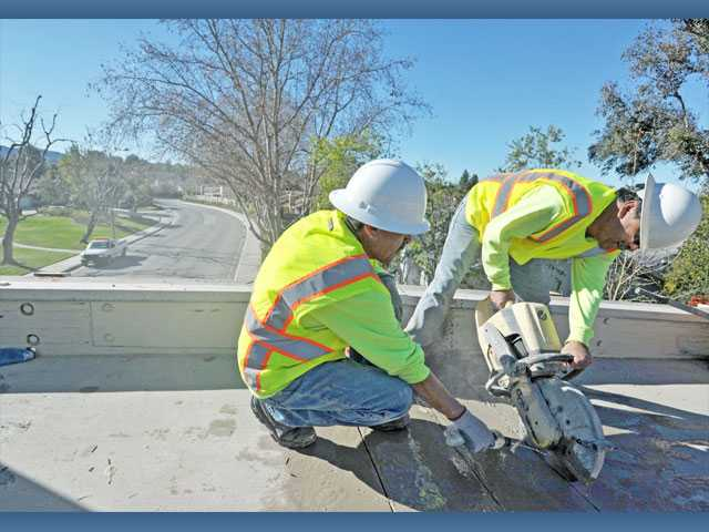 Daniel Verdugo, left, and Hector Chavez of Encorre Services Inc. cut through concrete to gain access to bolts on the paseo bridge over Alta Madera Drive near Paseo Lauro Court in Valencia on Monday. The bridge is being dismantled.