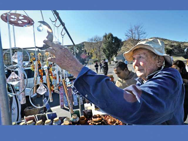 Vendor Ben Waldrop displays wind chimes at his booth at the Santa Clarita Swap Meet, held at the Saugus Speedway on Saturday.