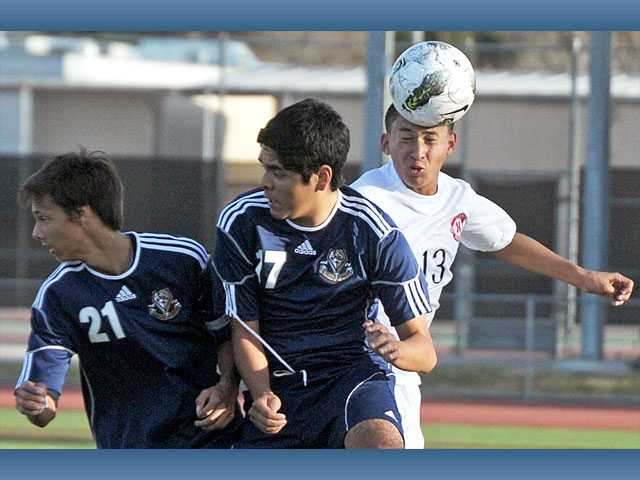 Hart midfielder Oscar Ocampo heads the ball as West Ranch's Brandon Dooley, left, and Angel Villegas defend on Tuesday at Hart High.