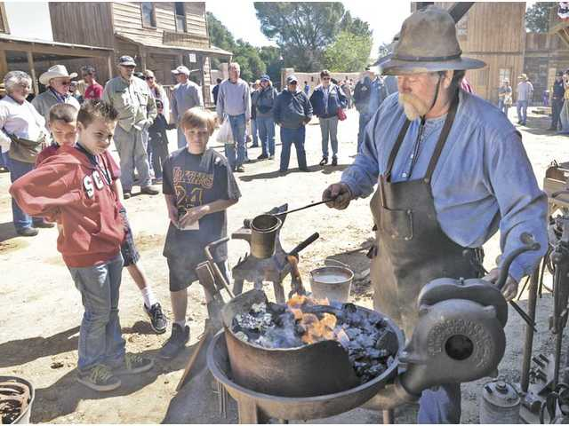 Talon Hudson, left, and brothers Paul Veluzat, and Noah, 9, behind,  watch as blacksmith Bryan Jones works on a horseshoe at the 2011 Cowboy Festival.
