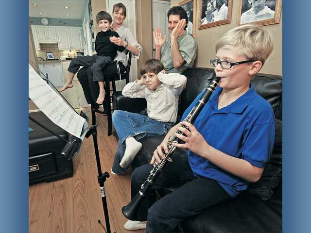 Adam practices his clarinet in front of his family, from left, brother David; mother, Diane; father, Martin; and brother Eric.