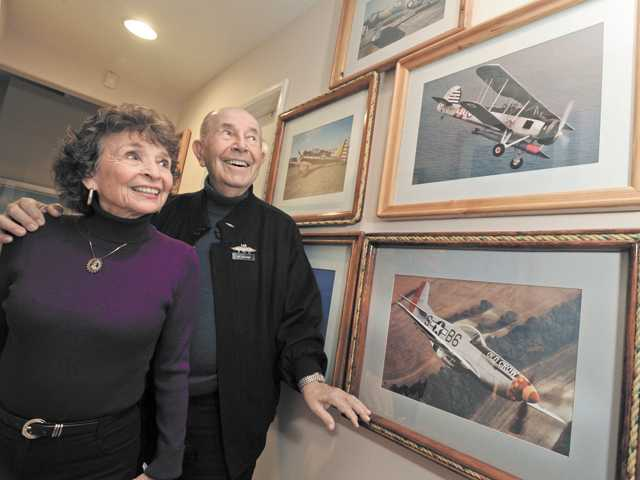Joyce and Lee Shulman in their Valencia home with framed photos of vintage aircraft.