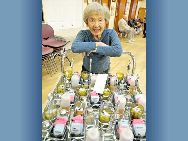 Ida Lee, 90, volunteers in the dining room.