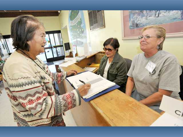 Ruby Griffin, 75, checks in for lunch with volunteer cashiers Linda Correa and Christine Birawer at the Santa Clarita Valley Senior Center in Newhall.