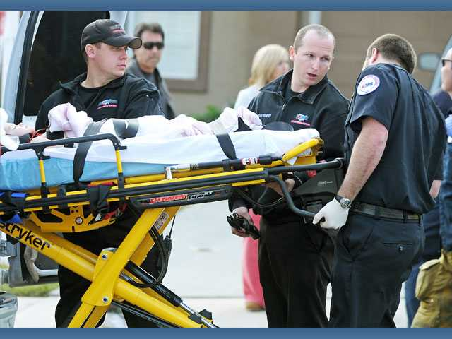 Emergency medical technicians transport a 2-year-old girl into a waiting ambulance in front of a home on the 28600 block of Oak Valley Road in Castaic on Monday.