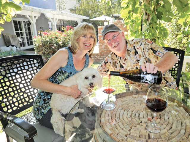 Nancy and Russ Riley, joined by their dog Gucci, enjoy a bottle of their wine under their backyard grape arbor at their home in Castaic.