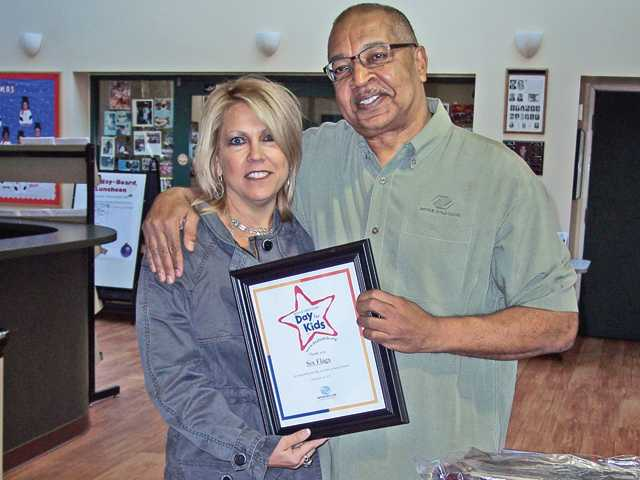"Ventress, right, presents Bonnie Rabjohn, president of Six Flags Magic Mountain and Hurricane Harbor, with a certificate of appreciation for participation in ""A Day for Kids."""