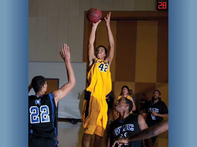 College of the Canyons' Tyler Barber (42) takes a shot as Santa Monica College's Eric Hayes looks on Wednesday at College of the Canyons.