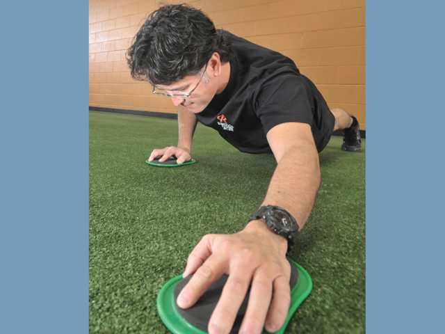 Hector Quinonez, of Castaic, demonstrates the Val Slide Push Away at Results Fitness in Newhall. Quinonez was part of the winning team of the 2011 New Year New You contest. His team lost 100 pounds during the six-week contest. Quinonez lost 28 pounds of fat.