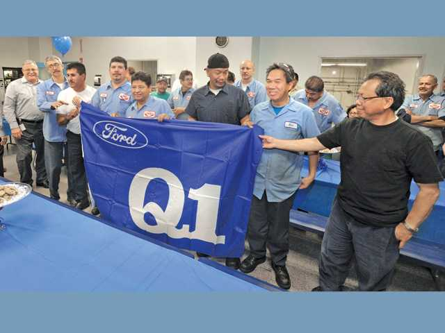AVK Industrial Products employees hold up a banner from Ford Motor Co. at AVK headquarters in Valencia on Thursday.