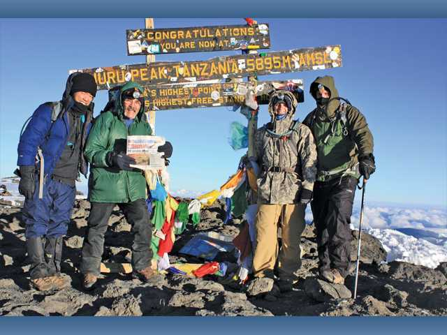 Chris Louie, Rawlins Jordan, Mark Jordan and Matt Jordan stand at the peak of Mount Kilimanjaro in the African nation of Tanzania.