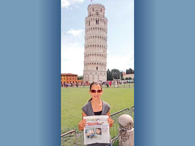 Dominique Nicolaides, an eighth-grader at Arroyo Seco Junior High School holds The Signal at the Leaning Tower of Pisa in Italy.