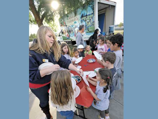 Recreation leader level three, Erin Weiss. left, hands out paper plates as a group prepares for a craft project near the Santa Clarita Parkmobile at Bridgeport Park in Santa Clarita on Thursday.