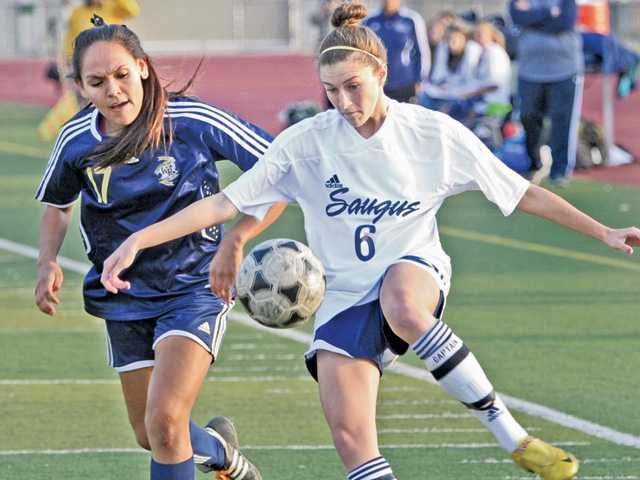 Saugus senior Stacy Atwater, right, receives a pass near the goal as West Ranch defender Lizet Pacheco follows on Friday at Saugus High School. Atwater scored a goal in the game but later left with an injury.