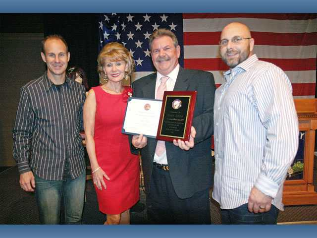 Left to right, Dale, Debbie, John and John Heys, Jr. display awards received by Elks Roastee John Heys. The event was held to benefit the Samuel Dixon Family Health Centers.