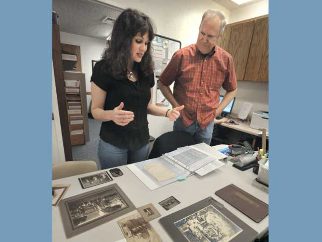 Kimberly Finley, left, and Kevin Large, director of Valencia Family History Center, discuss material gathered on Finley's father's ancestors at the center.