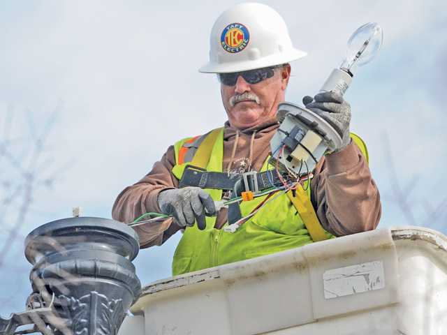 Taft Electric electrician Tim Jones pulls out the old high-pressure sodium light fixture as he prepares to install a more energy efficient induction filament lamp fixture in one of the 20 walkway lighting standards in the parking lot at Valencia Heritage Park in Valencia on Friday.