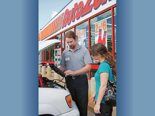 Auto Zone employee Manuel Zavala helps a customer at one its retail outlets in Cordova, Tenn.