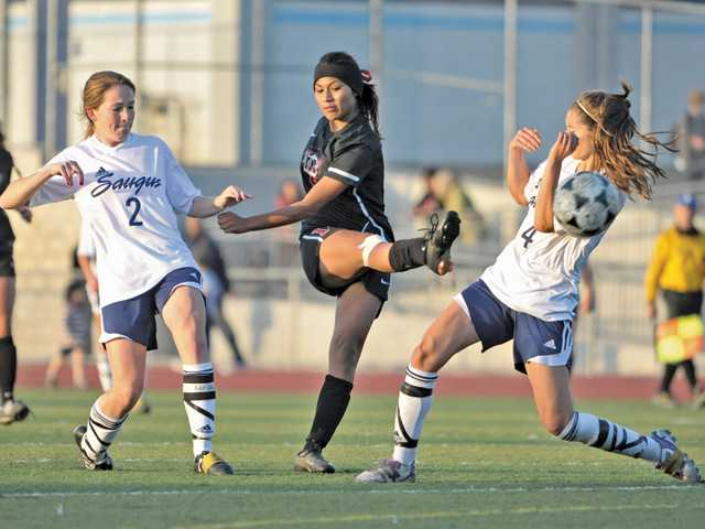 Hart High's Jenny Chavez, center, takes a shot on goal in between Saugus defenders Lizzy Rivas (2) and Nicolette Cascione (4) on Tuesday at Saugus High School.