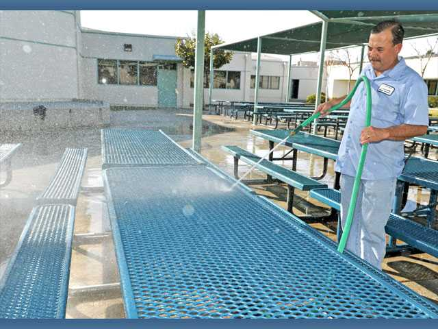 Custodian Sergio Diaz washes down lunch tables at Helmers Elementary School in Valencia on Wednesday. Diaz, who has been working at the school for 15 years, is one of four custodians who clean the campus' classrooms and offices.
